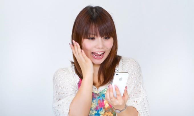 iPhoneを見て驚く女性